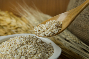 The Healthy breakfast cereal oat flakes in bowl on wooden table.