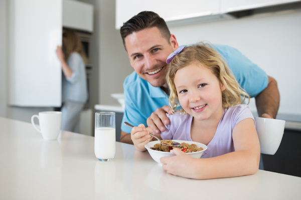 Portrait of happy father and daughter at breakfast table in house